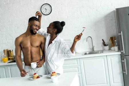 african american girlfriend touching boyfriend head at kitchen