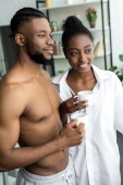 african american couple holding cups and looking away at kitchen