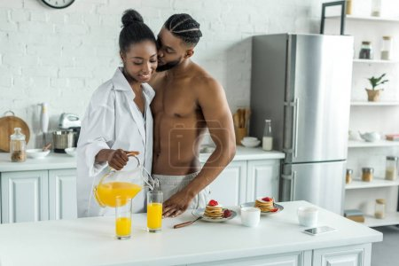 african american boyfriend kissing girlfriend while she pouring orange juice at kitchen
