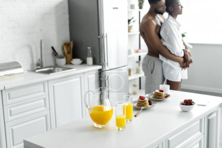 african american couple hugging with food on foreground at kitchen