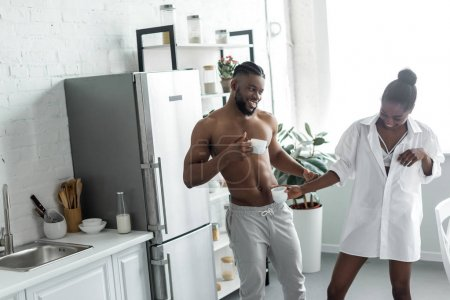 african american couple having fun with cups of coffee at kitchen