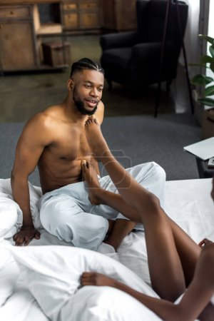 cropped image of african american couple sitting on bed in bedroom