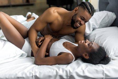 Photo pour Couple afro-américain souriant et câlin sur le lit dans la chambre - image libre de droit
