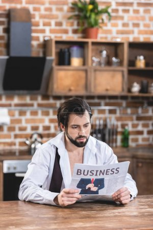 handsome loner businessman reading newspaper in morning at kitchen