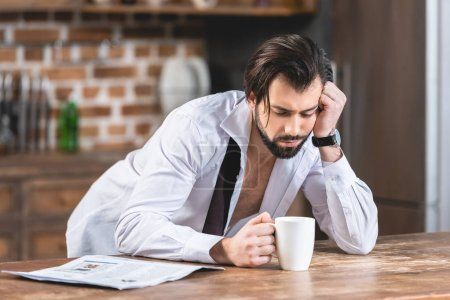 tired handsome loner businessman leaning on table with cup of coffee at kitchen