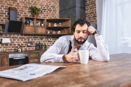 handsome loner businessman sitting with cup of coffee and sleeping at table at kitchen