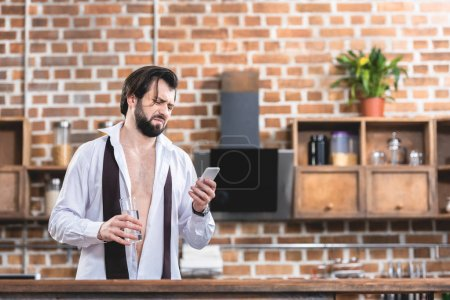 handsome loner businessman with hangover holding glass of water and looking at smartphone at kitchen