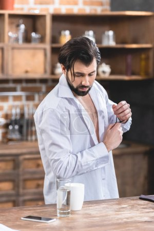 handsome loner businessman with unbuttoned shirt looking down at kitchen