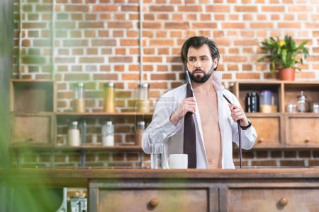 handsome loner businessman with unbuttoned shirt looking away at kitchen