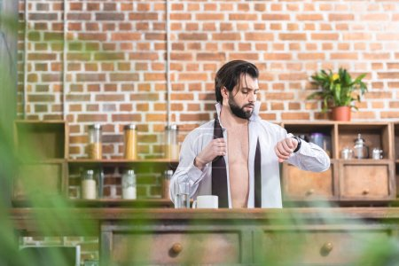 handsome loner businessman with unbuttoned shirt checking time at kitchen