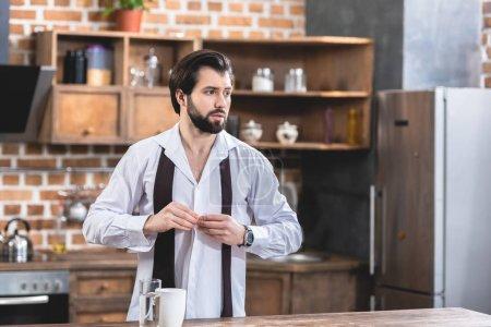 handsome loner businessman buttoning shirt at kitchen