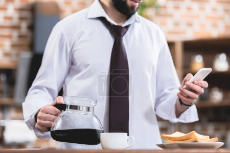 cropped image of loner businessman holding pot with coffee and smartphone at kitchen