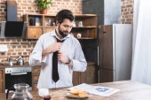 handsome loner businessman reading newspaper and fixing tie at kitchen