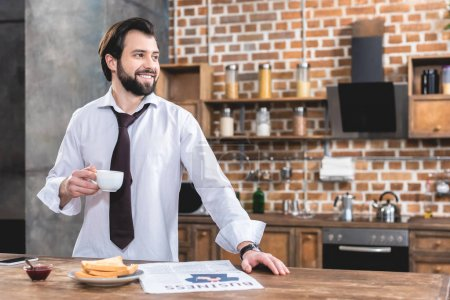 Photo for Handsome loner businessman holding cup of coffee and looking away at kitchen - Royalty Free Image