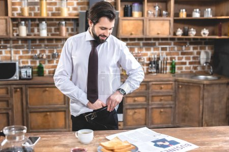 handsome loner businessman dressing for work at kitchen