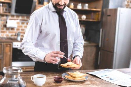 cropped image of loner businessman adding jam on toast at kitchen