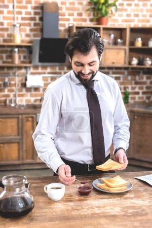 smiling handsome loner businessman adding jam on toast at kitchen