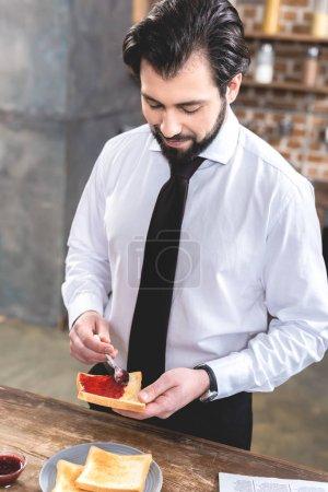 Photo for Handsome loner businessman adding jam on toast at kitchen - Royalty Free Image