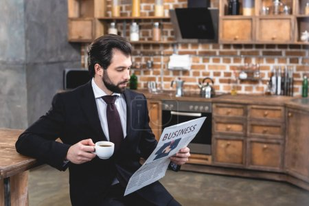 Photo pour Beau homme d'affaires solitaire lisant le journal et tenant une tasse de café le matin à la cuisine - image libre de droit