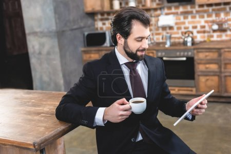 Photo for Side view of handsome loner businessman looking at tablet and holding cup of coffee at kitchen - Royalty Free Image