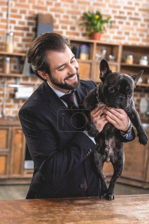 smiling loner businessman holding dog at kitchen
