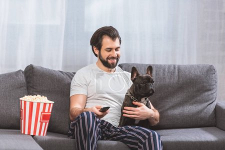 smiling handsome loner sitting with bulldog on sofa in living room