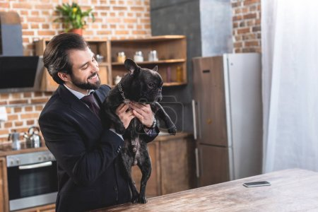 happy handsome loner businessman hugging bulldog at kitchen