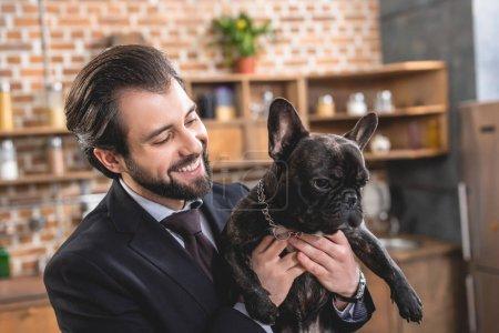 smiling handsome loner businessman hugging bulldog at kitchen