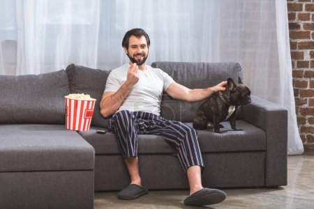smiling loner palming bulldog and eating popcorn on sofa in living room
