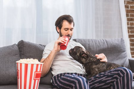 handsome loner palming dog and drinking beverage on sofa in living room
