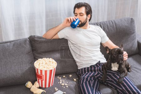 handsome loner palming bulldog and drinking beverage on sofa in living room