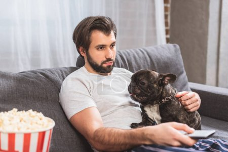 loner watching tv with with bulldog on sofa in living room