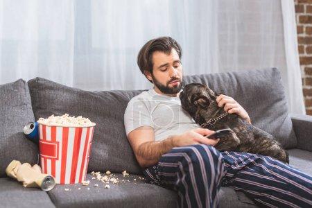 Photo pour Beau solitaire palming bulldog et la tenue de la télécommande sur le canapé dans le salon - image libre de droit