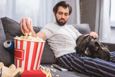 handsome loner sitting with bulldog and taking popcorn on sofa in living room