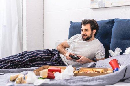 Foto de Solitario hombre feliz jugando videojuegos en el dormitorio - Imagen libre de derechos