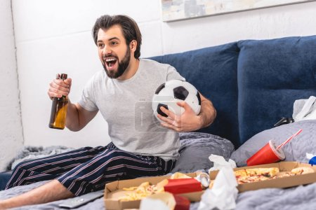 handsome loner watching football game with beer and screaming in bedroom