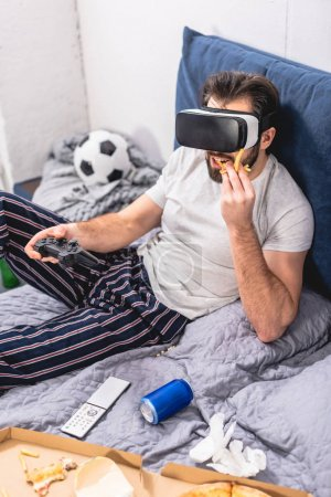 loner using virtual reality headset, playing video game and eating french fries in bedroom