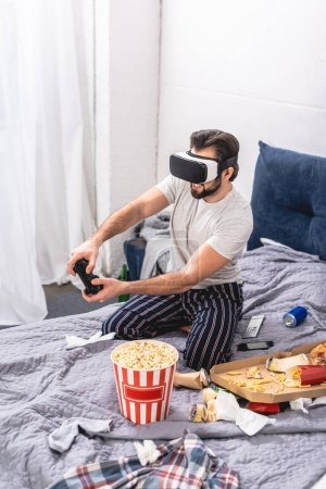 loner using virtual reality headset and playing video game on bed in bedroom