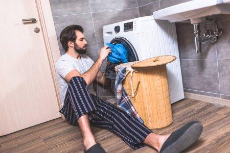 handsome loner putting laundry in washing machine in bathroom