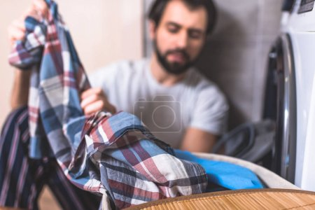 Photo for Handsome loner taking clothes for washing near washing machine in bathroom with shirt on foreground - Royalty Free Image