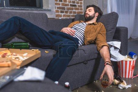 Photo pour Solitaire, dormir sur le canapé avec le verre de whisky dans salon sale - image libre de droit