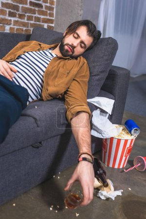 loner sleeping on sofa with glass of whiskey at living room