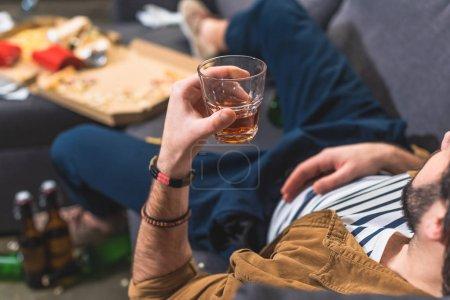 Photo pour Recadrée solitaire image allongée sur le canapé avec le verre de whisky au salon - image libre de droit