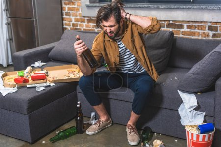 Photo for Loner with hangover looking at bottle of wine at living room - Royalty Free Image