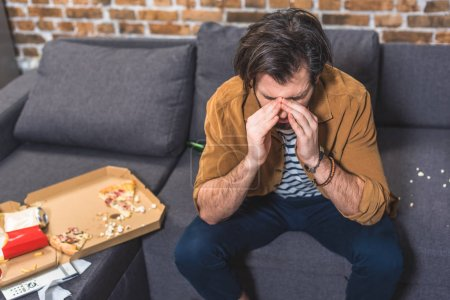 handsome loner having headache in morning and touching nose bridge at living room