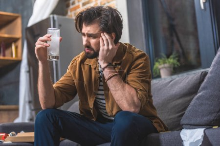 loner having headache and hangover and looking at glass of water with pill at living room