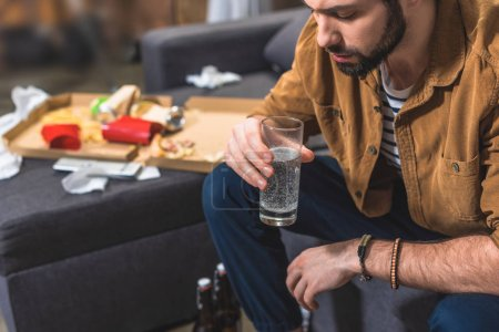 loner with hangover holding glass of water at living room