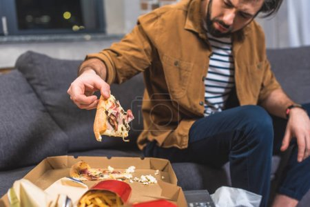 cropped image of angry loner taking piece of pizza at living room