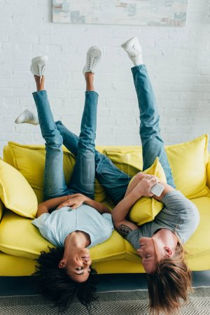 young woman with boyfriend holding smartphone and laying upside down on sofa