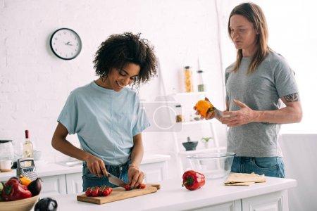 Photo pour Femme afro-américaine souriante coupant des tomates cerises à bord tandis que petit ami debout près avec poivron à la main - image libre de droit